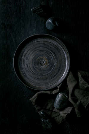 Empty black ceramic plate with black stones around on textile napkin over black wooden background. Flat lay, space.