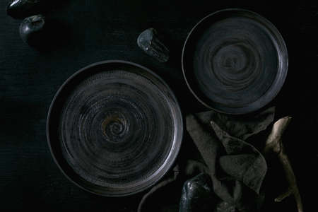 Set of empty black ceramic plates with black stones and wooden around on textile napkin over black wooden background. Flat lay.