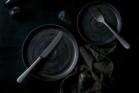 Empty black ceramic plates with cutlery and black stones around on textile napkin over black wooden background. Flat lay, space.