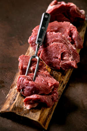 sliced raw beef tenderloin meat for steaks on wooden board with metal meat fork, salt and pepper over dark brown texture background. Food cooking background concept. Close up