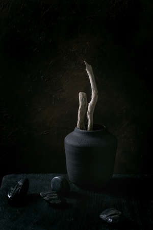 Dry wood branches in black ceramic vase on black wooden table with decorative stones. Dark still life. Copy space.