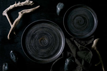 Empty black ceramic plates with black stones and wooden around on textile napkin over black wooden background. Flat lay.
