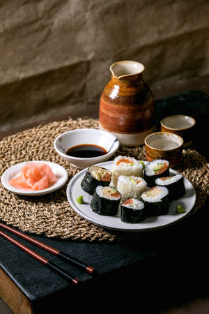 Homemade sushi rolls set with salmon, japanese omelette, avacado, ginger and soy sauce with chopsticks on straw napkin over balck wooden table. Ceramic drink sake set. Japanese style dinner