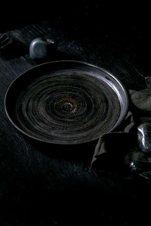 Empty black ceramic plate with black stones around on textile napkin over black wooden background.