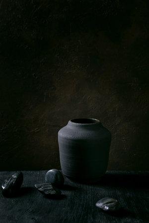 Empty black ceramic vase on black wooden table with decorative stones. Dark still life. Copy space.