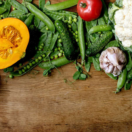 Variety of fresh raw organic vegetables for cooking. Half of hokkaido pumpkin, young green pea, cauliflower, garlic, cucumbers , tomatoes over wooden background. Farmer market concept. Flat lay, space. Square