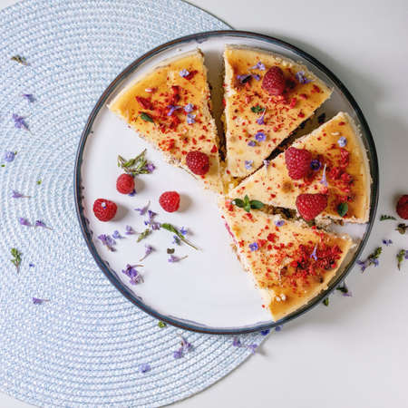 Sliced homemade raspberry baked cheesecake on plate decorated by fresh raspberries, edible flowers and mint on round napkin over white background. Flat lay, space. Square