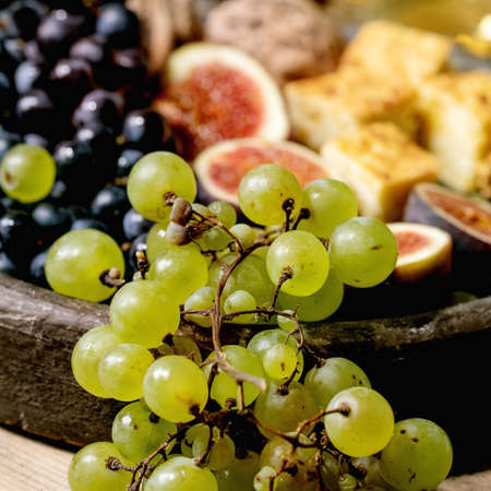 Wine appetizers with different grapes, figs, walnuts, bread, honey and goat cheese on ceramic plate, serving with glasses of red and white wine over old wooden background. Close up. Square