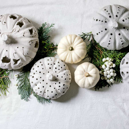 Holiday decoration with white decorative pumpkins, craft clay pumpkins, thuja branches over old wooden background. Flat lay, copy space. Square