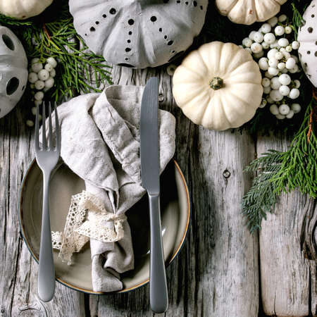 Holiday table setting decoration with white decorative pumpkins, craft clay pumpkins, thuja branches, empty plate with cloth napkin, cutlery over old wooden table. Flat lay, space. Square