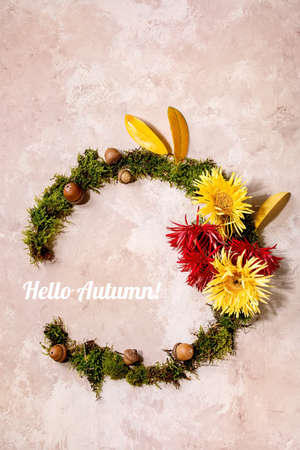 Beautiful Autumn botanical wreath composition creative layout with flowers, moss and yellow autumn leaves over beige concrete background. Flat lay, copy space. Hello Autumn inscription 版權商用圖片