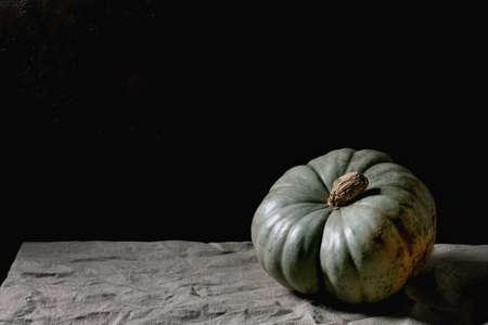 Blue pumpkin on linen tablecloth. Dark still life. Autumn harvest. Copy space 版權商用圖片