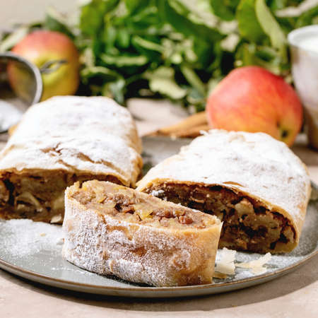 Homemade sliced classic apple strudel with icing sugar on ceramic plate with fresh apples, green leaves and cinnamon sticks above. Close up. Square