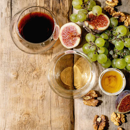 Glasses of red and white wine with grapes, figs, goat cheese and walnuts over old wooden background. Flat lay, copy space. Square