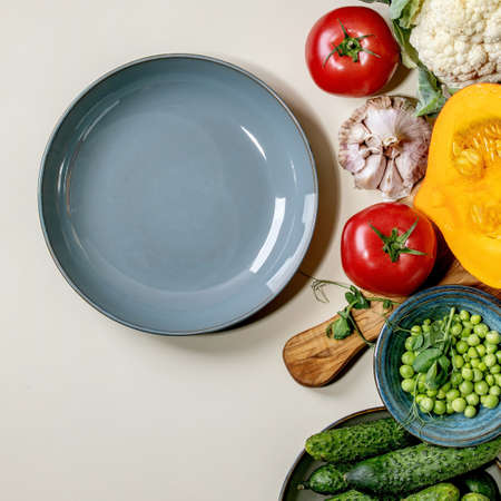Variety of fresh raw organic vegetables for cooking. Half of hokkaido pumpkin, young green pea, cauliflower, cucumbers and empty plate over beige background. Healthy eating concept. Flat lay, space. Square 版權商用圖片