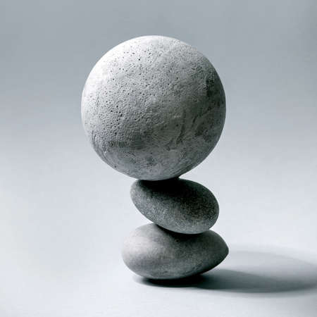 Abstract background with composition of balanced grey geometric objects sphere and stones. Copy space. Modern concept for product presentation. Square