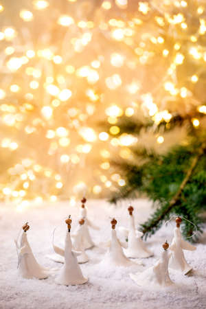 Porcelain Christmas angels. Set of craft handmade Christmas decoration on snow with bokeh holiday lights and fir tree branches.