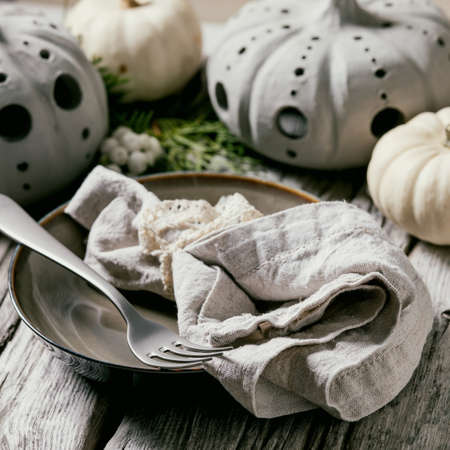 Holiday table setting decoration with white decorative pumpkins, craft clay pumpkins, thuja branches, empty plate with cloth napkin, cutlery over old wooden table. Close up. Square