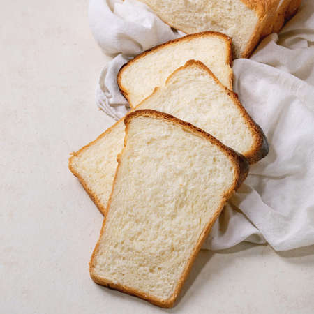 Sliced homemade Hokkaido wheat toast bread on white cloth on white texture background. Flat lay, copy space. Square