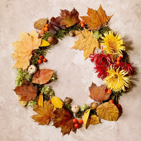 Beautiful Autumn botanical wreath composition creative layout with flowers, moss and yellow autumn leaves over beige concrete background. Flat lay, copy space. Square 版權商用圖片
