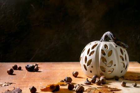 Halloween or Thanksgiving decorations, white handcrafted carved ceramic pumpkin standing on orange stone table with autumn leaves and acorns. Halloween holiday interior home decor. Copy space
