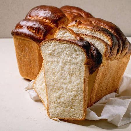 Homemade Hokkaido wheat toast bread whole and sliced on white cloth on table. Square