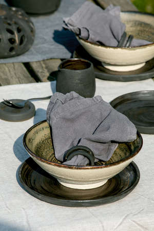 Rustic table setting outside in garden with empty craft ceramic tableware, black plates and rough bowls, pumpkin decorations, on linen tablecloth over old wooden table. Garden party. Close up 版權商用圖片