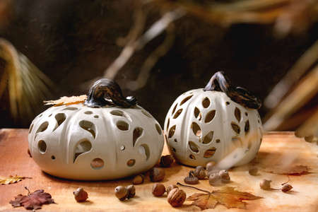 Halloween or Thanksgiving decorations, set of white handcrafted carved ceramic pumpkins standing on orange stone table with autumn leaves and acorns. Halloween holiday interior home decor