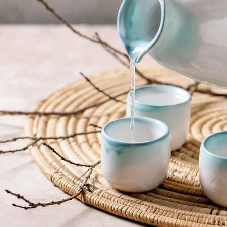 Sake ceramic set for traditional japanese alcohol drink rice wine sake pouring from pitcher in three cups, standing on straw napkin with dry branches over beige texture background. Square