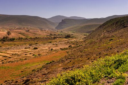 a valley of a dry river in the south of morocco near Sidi Ifni. A settlement in a distance.