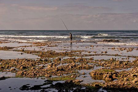 Atlantic ocean, surf at the beach near Legzira and a man sea fishing