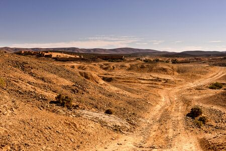 A rough piste leading to fort bou sherif. the landscape is hilly. Fort Bou Sherif is in the distance.