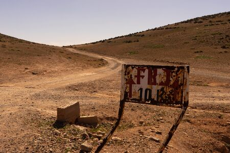 a track to the south near sidi ifni, morocco. the piste leads to the horizon. A street sign leading to fort bou sheriff Reklamní fotografie