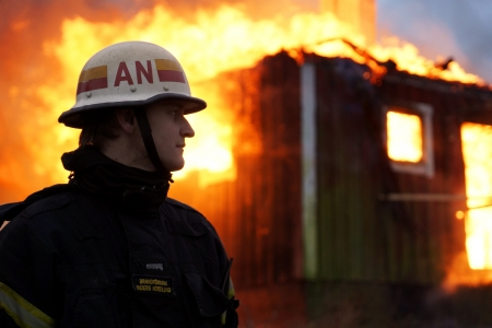 Firefighter in front of burning house without face mask Stock Photo - 17269385