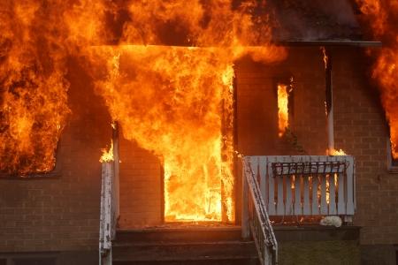 incendio casa: Una casa de ladrillo en el fuego con llamas que salen de todas las aberturas