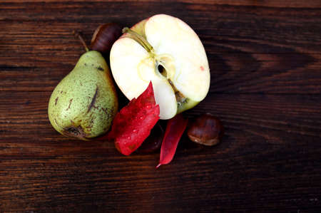 Autumn decor, red leaves, pear, apple and chestnuts on a wooden board Reklamní fotografie