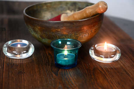 A tibetan singing bowl with lighted candles