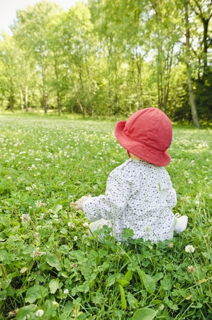 Baby girl sitting in meadow watching the nature photo