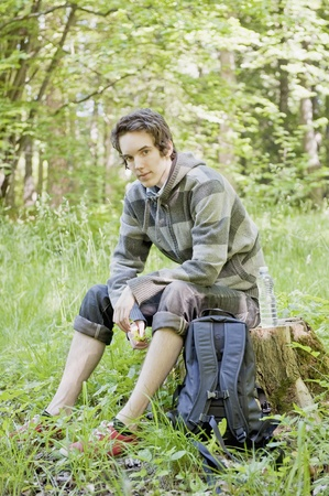 Young man resting during a trek in the woods Stock Photo