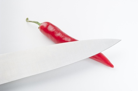red chili pepper: Knife on top of a red chili pepper