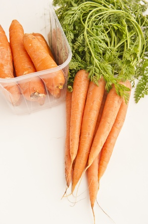 A bunch of organic carrots an non-organic carrots in a plastic container Stock Photo - 11068182