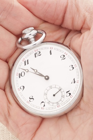 Hand holding an old fashioned pocket watch