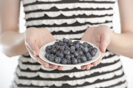 Studio shot of a young woman holding a plate with blueberries Stock Photo - 11957929