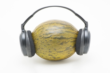 Melon with headphones on white background Stock Photo