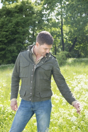Man standing in a meadow and picking a flower Stock Photo - 14249354