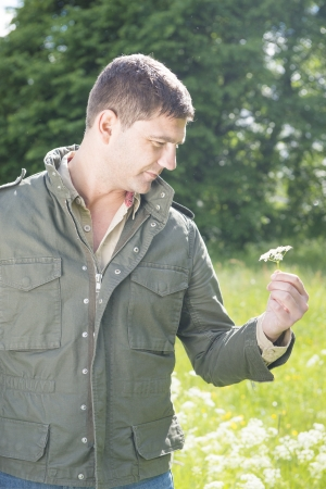 Man standing in a meadow and picking a flower Stock Photo - 14249350