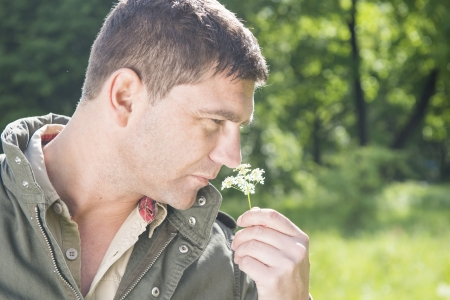 unworried: Man standing in a meadow and picking a flower