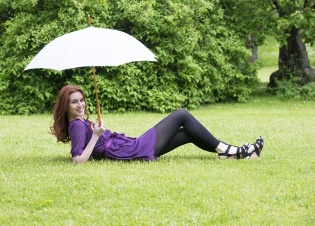 unworried: Young woman lying in a park and shielding the sun with a white umbrella Stock Photo