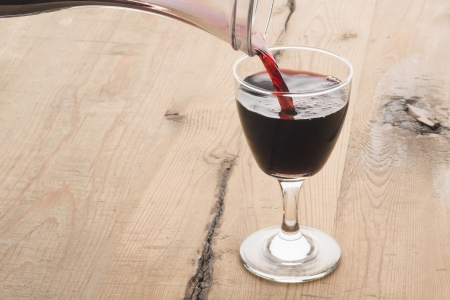 A glass of red wine being filled from a carafe photo