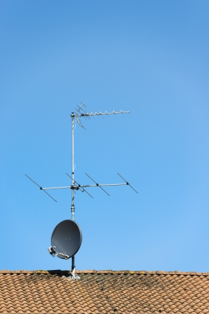 Aerial and satellite dish on roof of house with clear blue sky above Stock Photo
